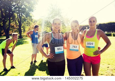 fitness, sport, friendship, marathon and healthy lifestyle concept - happy young sporty women with racing badge numbers outdoors
