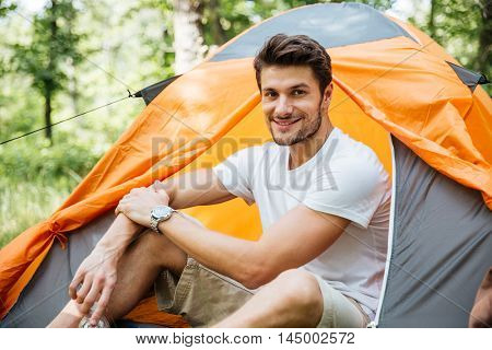 Cheerful young man tourist sitting in touristic tent in forest
