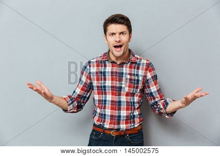Angry irritated young man t-shirt over gray background