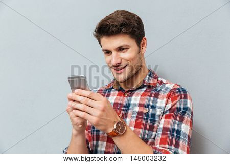 Happy young man in plaid shirt using cell phone over grey background