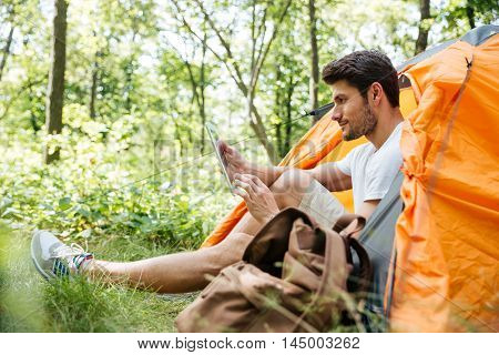Serious young man tourist sitting at touristic tent and using tablet in forest