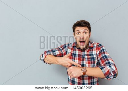 Amazed young man in plaid shirt pointing on wristwatch over grey background
