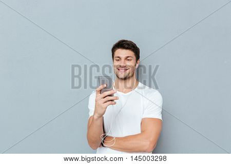 Happy attractive young man listening to music from smartphone over gray background