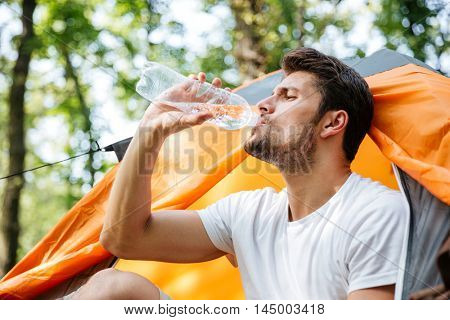 Closeup of attractive young man tourist sitting and drinking water in touristic tent at forest