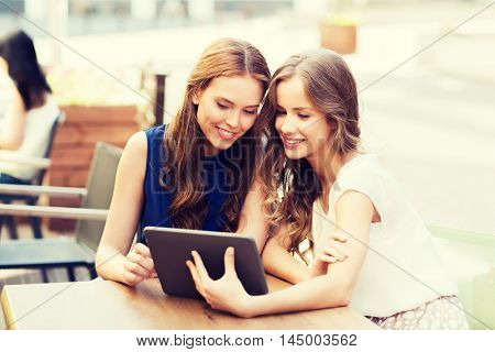 technology, lifestyle, friendship and people concept - happy young women or teenage girls with tablet pc at cafe outdoors