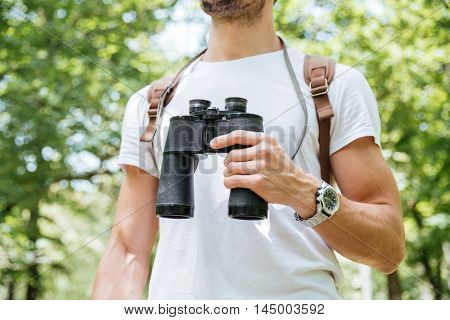 Closeup of young man with backpack standing and holding binoculars in forest