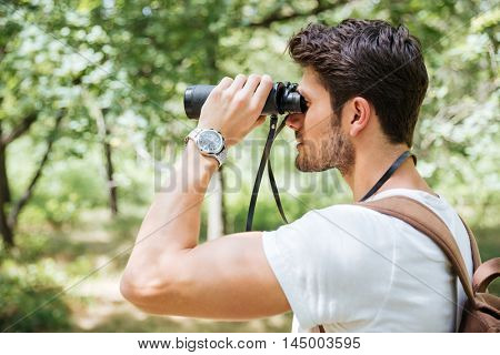 Attractive young man with backpack looking through binoculars outdoors