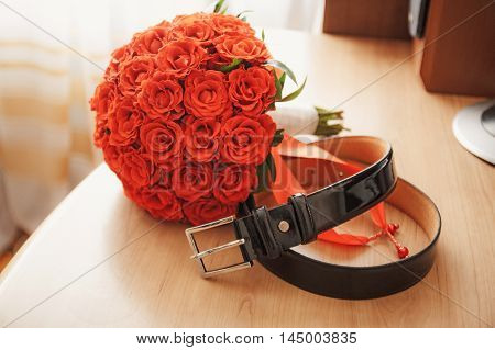 Wedding men's belt in place with a bouquet