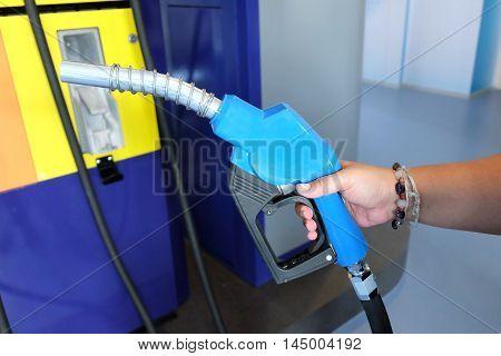 Hand holding blue fuel nozzle. Fuel pumps petrol.