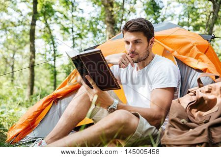 Thoughtful young man tourist sitting and reading book in touristic tent in forest