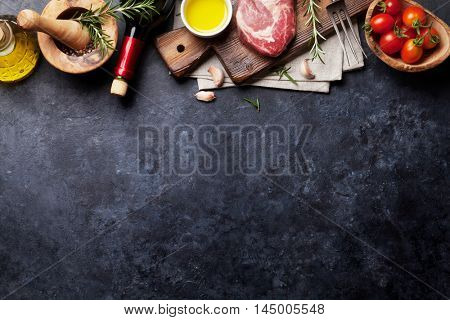 Raw beef steak cooking and ingredients. Meat piece, red wine, herbs and spices. Top view with copy space over stone table