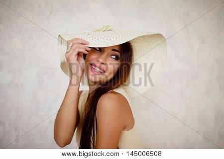 Portrait of beautiful lovely brunette woman in white sundown holding it's brim on white background