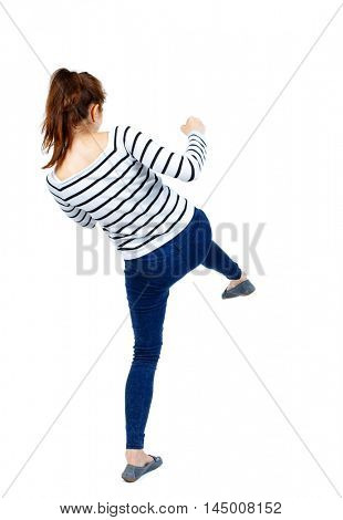 back view of woman funny fights waving his arms and legs. Rear view people collection. Girl in a striped sweater's back and hits his foot.
