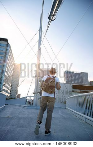 Man In Fedora With Vintage Backpack On A Bridge