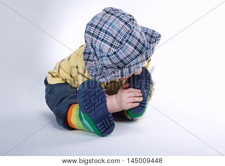 photo of little boy bites his leg