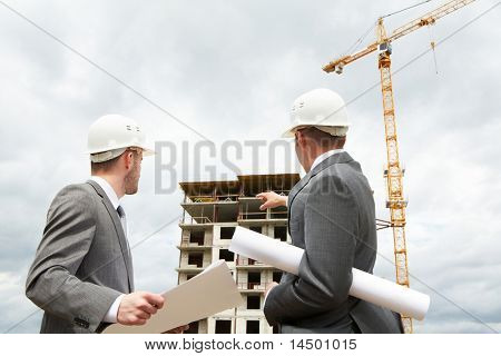 Photo of young engineer showing something to his partner at building site