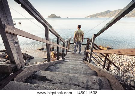 Man Stands On Old Wooden Stairway, Sea Coast