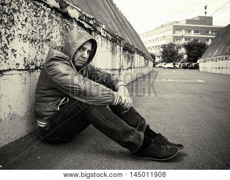 Sad Man sit near the Brick Wall.  Black and white photo