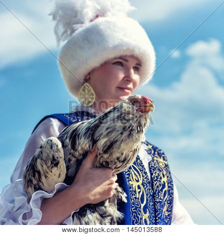 Kazakh bride in festive national dress. Portrait of a rooster in his hands.