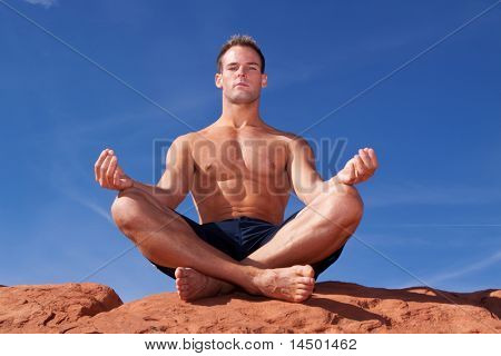 Muscular man meditating on red rocks