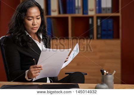 Portrait of concentrated Asian business lady analyzing document