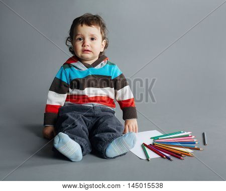 photo of little unhappy boy with pencils