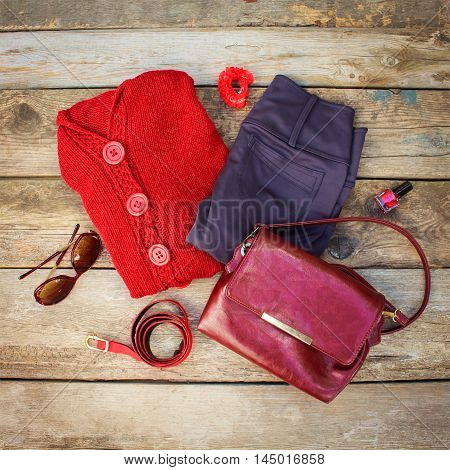 Women's autumn clothing and accessories: red sweater, pants, handbag, beads, sunglasses, nail polish, hair band, belt on wooden background. Top view.