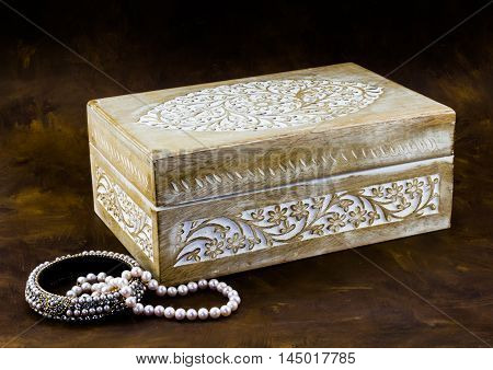Antique carved pale wood box with peal jewellery on dark brown background