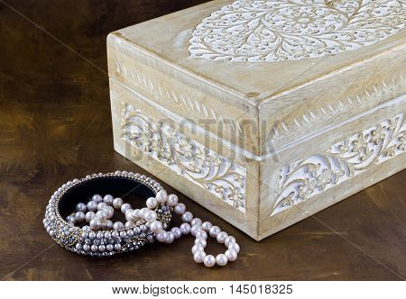 Old chalk painted carved wood jewelry box with pearl bangle and pearls