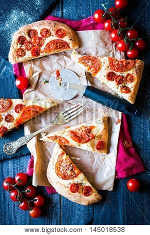 Tasty Hand Made Tomatoes  Pizza Bread with italian style recipe over a wooden table with a Dramatic light.