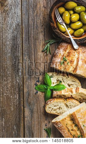 Green mediterranean olives in bowl and slices of freshly baked ciabatta over rustic wooden background. Top view, copy space,