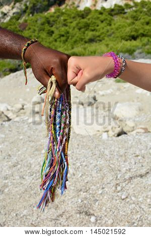 Hands of different races adorned with traditional African bracelets making fist to fist agreement and bunch of African bracelets vertical orientation