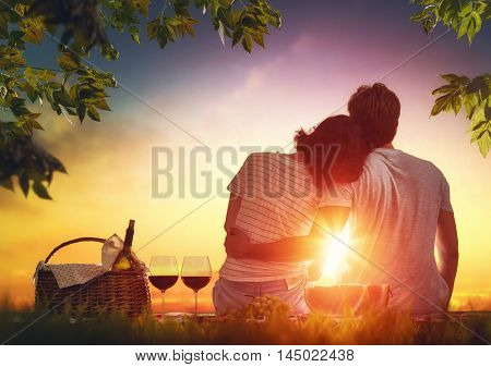 Happy couple in love. Stunning sensual portrait of young stylish fashion couple picnicking together on green grass in summer park.