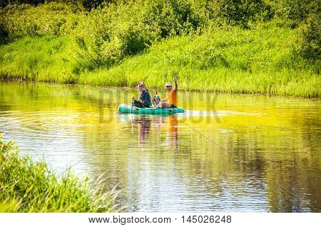 Family with children ride inflatable rubber boat on the river .