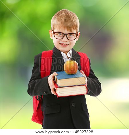 Little boy with backpack holding books and apple on blurred green background. School concept.