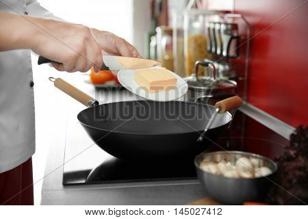 Female hand putting butter in pan closeup