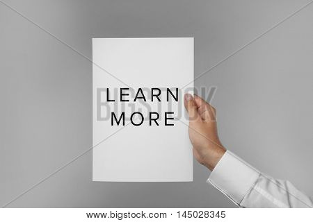 Man's hand holding white paper on light background. Business trainer