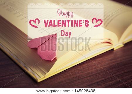 Origami heart bookmark on book page. Text happy valentines day.