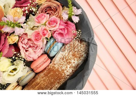 Gift box with flowers and cookies on wooden background