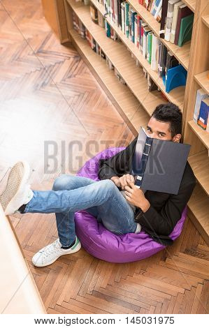 Top view of handsome man sitting on the floor near bookshelves and reading books in library.