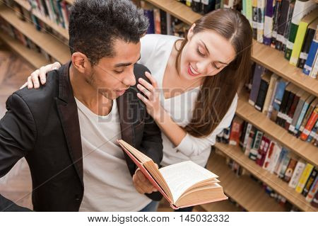Top view of students communicating in library. American man explaining to his girl-friend something important in science.