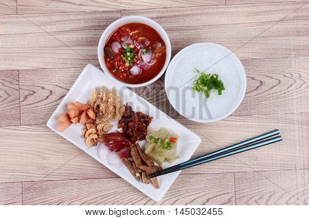 Rice gruel and  side dish  on wood. (Dried shredded pork,Chinese sausage,crispy fish,sausage, fried baby clams,sliced red onion,pickle Chinese cabbage ,Spicy sardine salad and shallots )