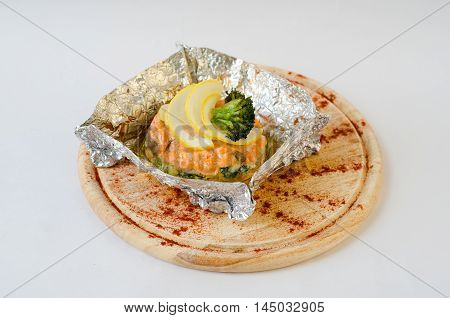 Salmon steak baked in foil with broccoli