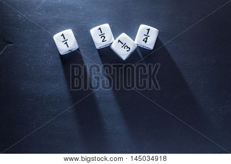 white fraction math number dices on blackboard good for background and teaching blogs with harsh lighting showing long dices' shadows and selective focus on dices room for copyspace on top of frame