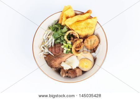 Steam pork hock and egg with noodle in brown sauce in white background.