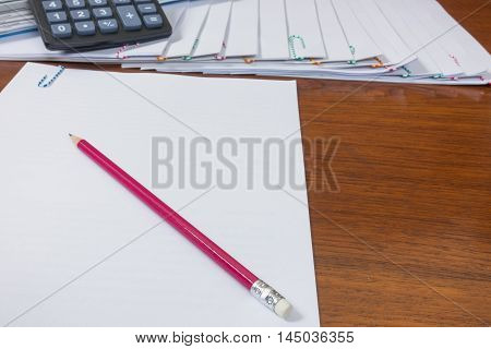 pencil reports arranged and document place with paperclip have calculator on wooden floor.