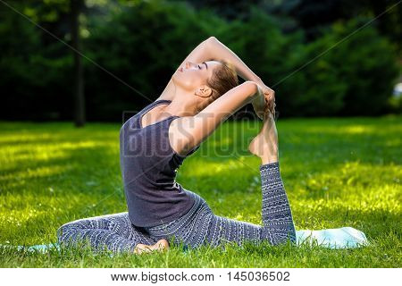 Young fitness woman meditation in a city park.Yoga at sunset in the park. Girl is practicing yoga. Fitness training outdoors. Attractive fitness woman. Workout outdoors. Healthy lifestyle