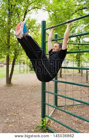 Young athlete exercising on outdoor stall bars