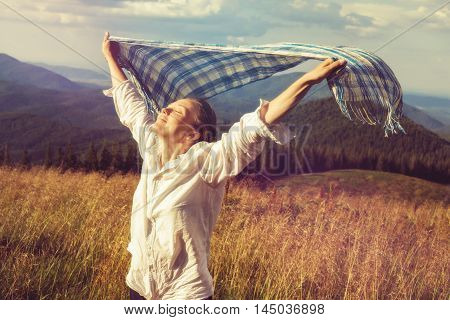 Young woman with fluttering scarf runs towards the sun enjoying life. Toned image. Vintage