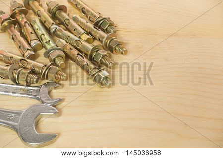 wrench Bolts and screws used in construction on the wood background.